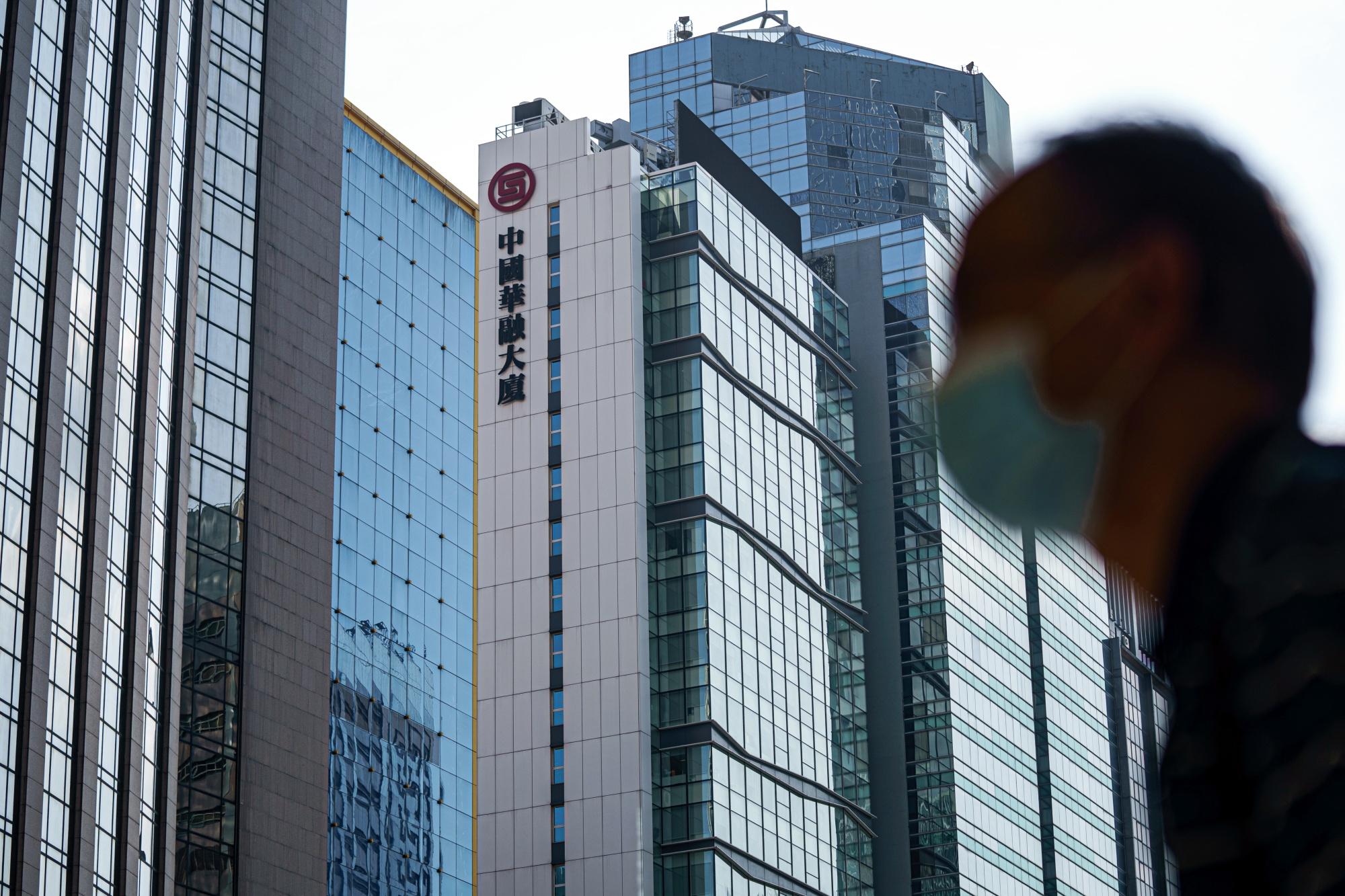 A pedestrian walks past the China Huarong Tower in Hong Kong.
