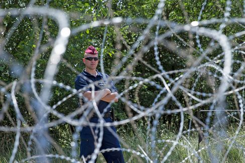 A Hungarian soldier stands guard on the country's border with Serbia in an effort to manage refugees, in Szeged, Hungary, on July 16, 2015.