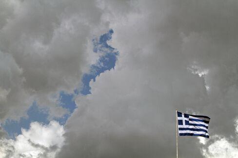 A Greek National Flag Flies Beneath A Couldy Sky