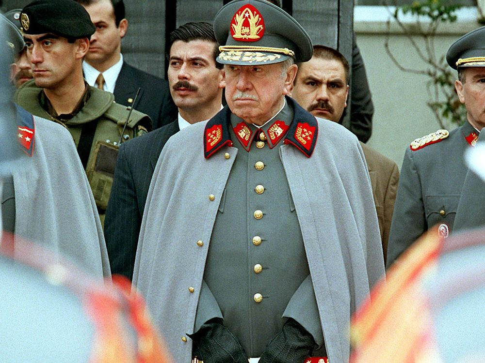 Augusto Pinochet listens to a military band playing before his residence in Santiago on Sept. 11, 1997.