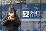 A pedestrian uses a smartphone in front of an Alipay sign outside an Ant Group Co. office building in Shanghai, China, on Thursday, Dec. 24, 2020.