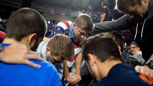 Liberty University students pray beforeSanders's speech.