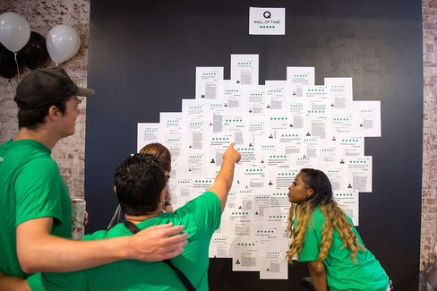 Employees look at positive feedback posted on the Q Wall of Fame during a team meeting.