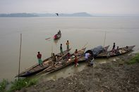 Fishermen arrive on boats to the bank of the river