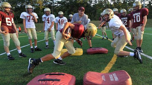 CONCORD, MA - AUGUST 16: Kevin Smith, President of Concord-Carlisle Pop Warner Football, center, coaches a one-on-one drill during practice.