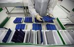 An employee performs a final inspection on solar cells on the production line at the Trina Solar Ltd. factory.
