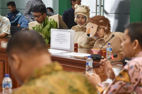 Activists wear animal outfits during a protest at the judicial commission office against the Sumatran district courts decision to reject a lawsuit to plantation company over its alleged involvement in a forest fire.