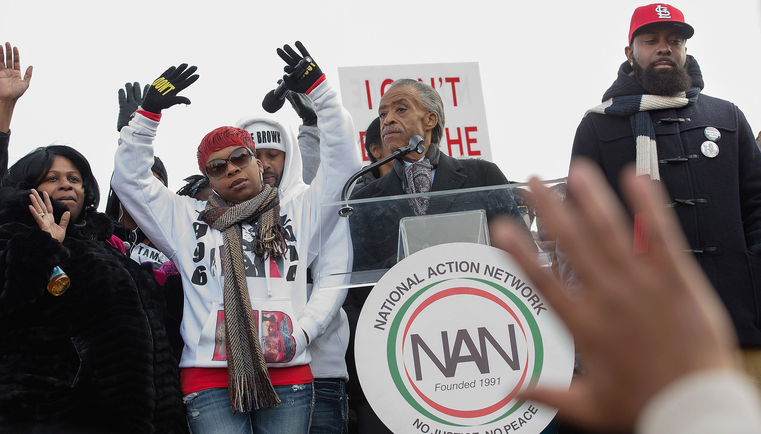 Samaira Rice, the mother of Tamir Rice; Lesley McSpadden, the mother of Michael Brown Jr; Rev. Al Sharpton and Michael Brown Sr., the father of Michael Brown Jr, raise their hands in the air during the 'Justice For All' march and rally through the nation's capital December 13, 2014 in Washington, DC.