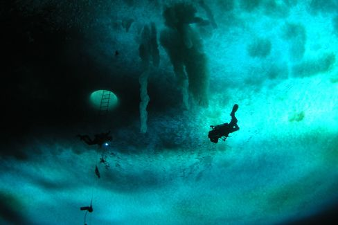 A diver ascends to the bottom of the sea ice at Cape Evans Wall, in Antarctica