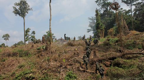 UN and Congolese soldiers climb hill at captured ADF camp on Aug. 26.