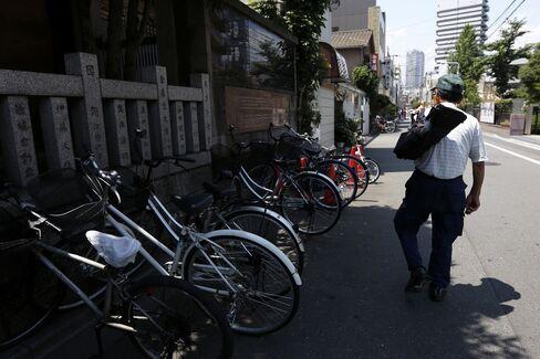 An Elderly Man Walks Past Bicycles in Tokyo