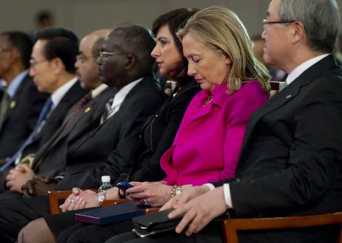 Clinton checks her BlackBerry alongside Korean Foreign Minister Kim Sung-hwan as she attends the Fourth High Level Forum on Aid Effectiveness in Busan, Korea, on Nov. 30, 2011.