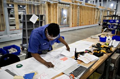 Robots may help build your next home and fill the labor gap an electrician checks her blueprint at the baltimore robotics facory malvernweather Image collections