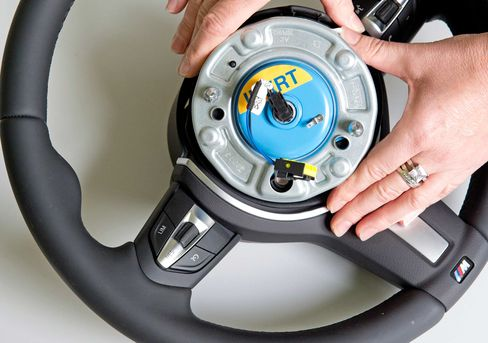 A worker shows anair bag initiator at Takata Ignition Systems in Schoenebeck, Germany, on April 17, 2014.