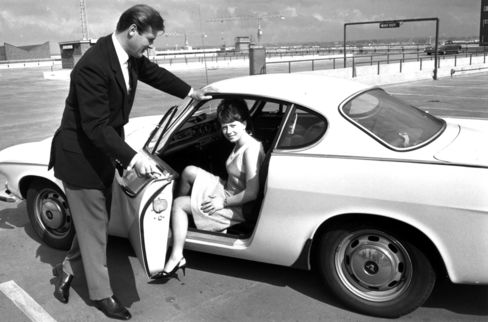 Roger Moore opens the door of his Volvo for Isabelle McMillan in a 1965 scene from 'The Saint.'