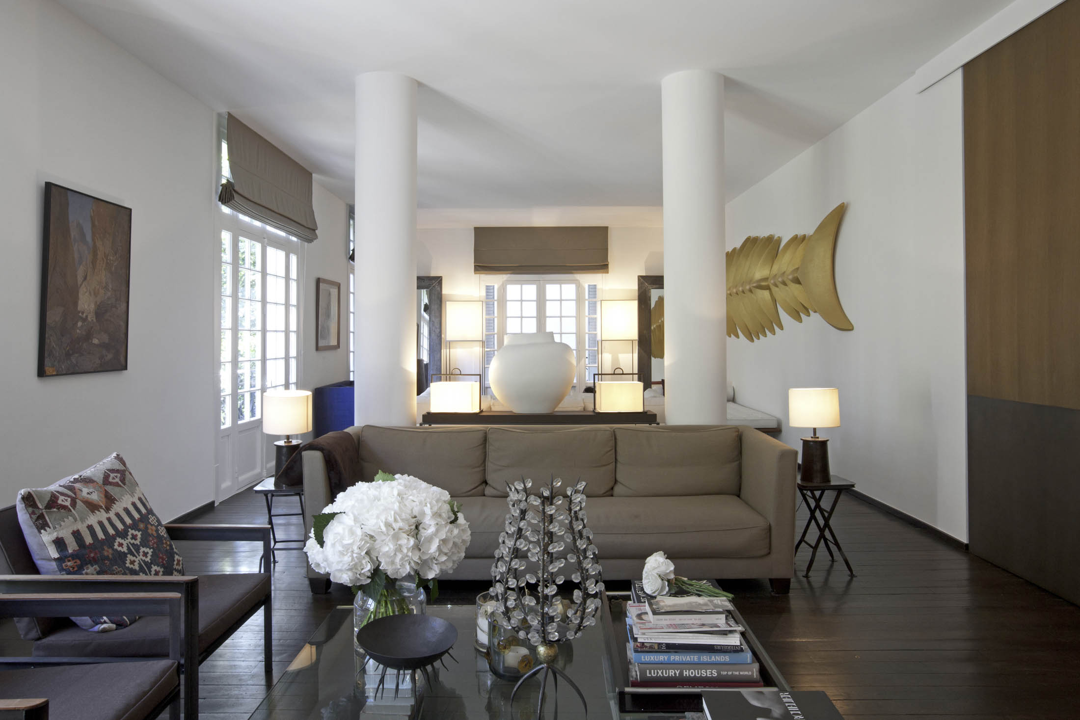The living room's eclectic mix of furniture and objects includes a gold fish skeleton.