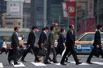 Office workers walk across an intersection in Tokyo, Japan.