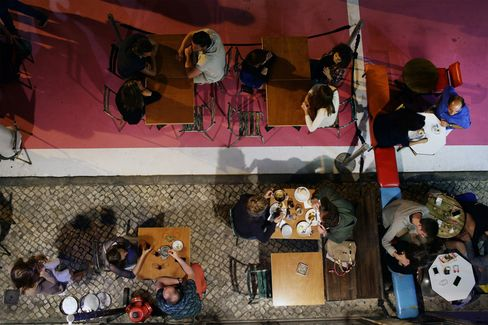 Tourists dine at outdoor tables on