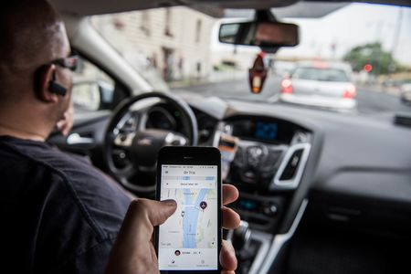 A passenger holds an Apple Inc. iPhone displaying the Uber Technologies Inc. car service taxi application (app) journey progress screen in this arranged photograph in Budapest, Hungary, on Wednesday, July 13, 2016. Uber will suspend its ride-hailing services in Hungary from July 24 following a government decision to pass a bill that allows authorities to block access to the mobile application and fine media promoting it. Photographer: Akos Stiller/Bloomberg