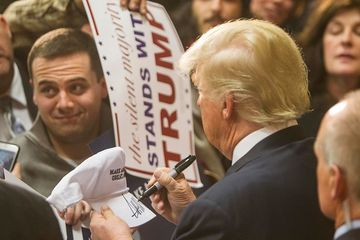 Republican presidential candidate Donald Trump signs a hat after speaking at Stevens High School on Jan. 5, 2016, in Claremont, New Hampshire.