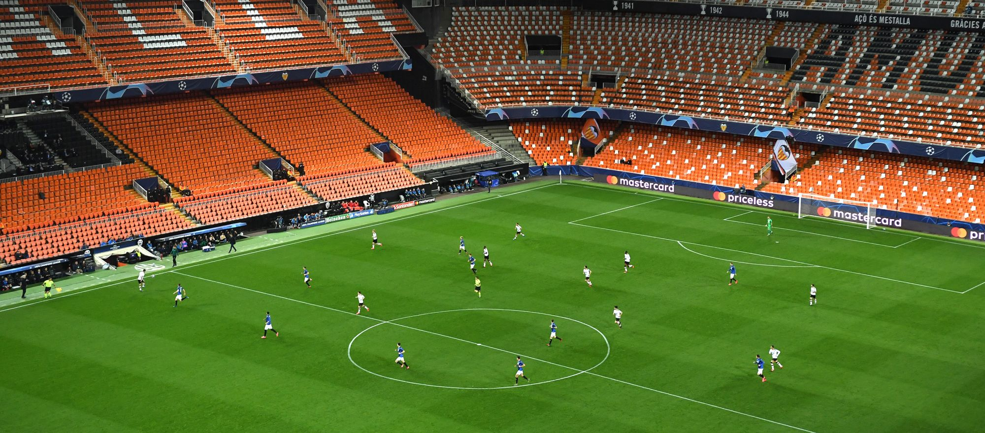 Wide angle image of players playing inside a pitch without spectators
