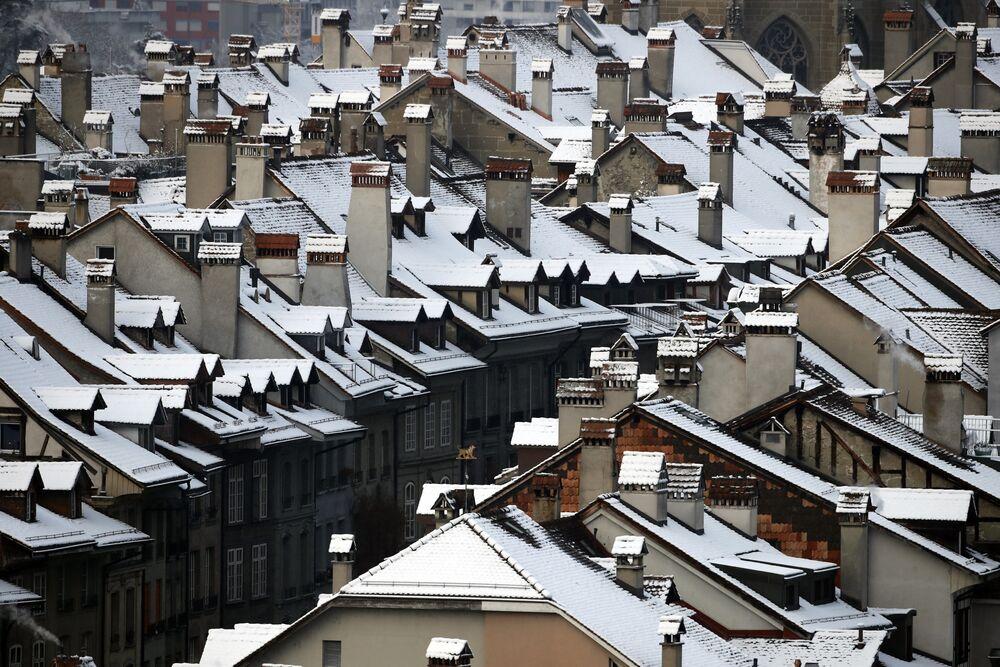 La neve si trova sui tetti delle tradizionali proprietà residenziali svizzere nel centro storico di Berna.