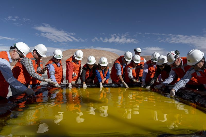 Visitors inspect a brine pool at a Sociedad Química y Minera de Chile (SQM) lithium mine on the Atacama salt flat in the Atacama Desert, Chile on May 29, 2019.