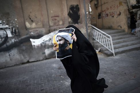 A Bahraini woman holds a poster bearing a portrait of prominent Shiite Muslim cleric Nimr al-Nimr during a protest against his execution by Saudi authorities.