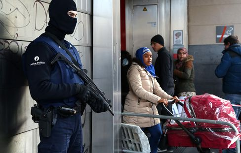 A Belgian police officer stands guard outside the De Brouckere metro station in Brussels, on March 23, 2016.