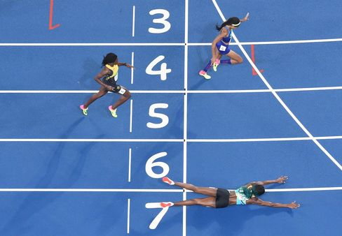 The Bahamas' Shaunae Miller dives to cross the finish line ahead of USA's Chase Kalisz during the women's 400-meter final.