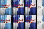 Cans of Red Bull GmbH energy drink sit on display inside asupermarket in Redhill.
