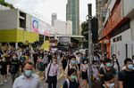 Pedestrians wearing protective masks walk across a road in Hong Kong, China, on Friday, July 10, 2020.