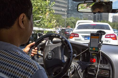 A taxi driver is using Didi Dacha App while driving on the