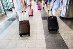 Travelers pull luggage while walking through LaGuardia Airport (LGA).