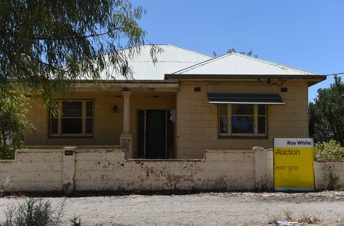 An auction sign stands on the edge of a residential property in the township of Broken Hill.