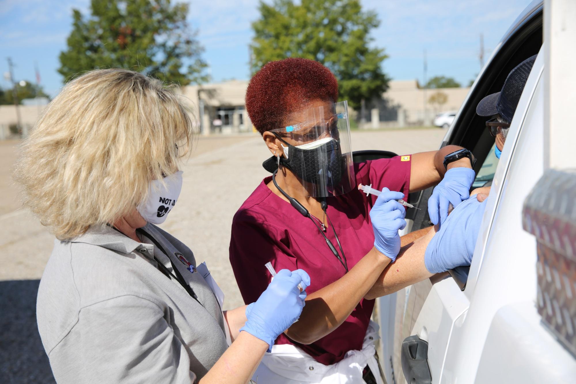 W czwartek, 5 listopada 2020 r., Pracownicy służby zdrowia podają szczepionki przeciw grypie w klinice dla kierowców na grypę w Louisiana State Fairgrounds w Shreveport w stanie Luizjana w USA. Fotograf: Dylan Hollingsworth / Bloomberg
