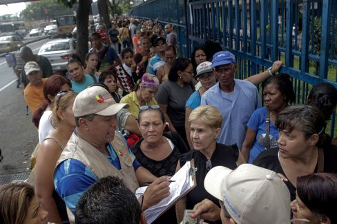 Venezuela faces a deepening economic crisis as low oil prices strangle export revenue. Caracas residents line up outside a store for scarce groceries.