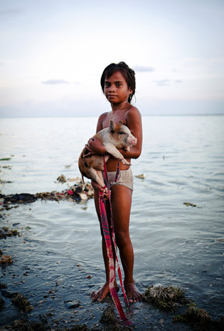 A girl and her pig in the fetid waters of Bairiki, a densely populated slum in Tarawa, the nation's capital