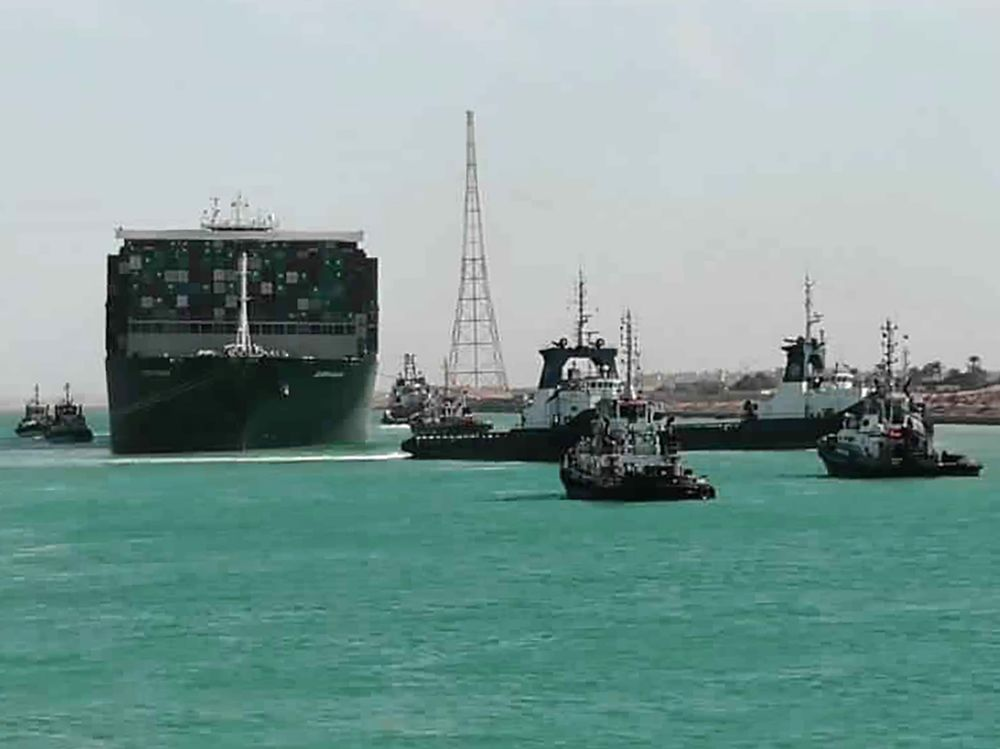 Tugboats tow the Ever Given along the Suez Canal on March 29.