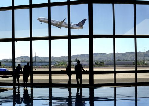 Airline passengers waiting for their flights watch from the terminal as a United Airlines airplane takes off at Phoenix Sky Harbor International Airport in Phoenix, Arizona.