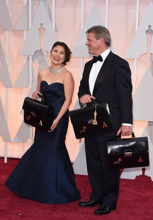 Martha Ruiz and Brian Cullinan carry the envelopes of the winners on the red carpet for the 87th Oscars on Feb. 22, 2015, in Hollywood, Calif.