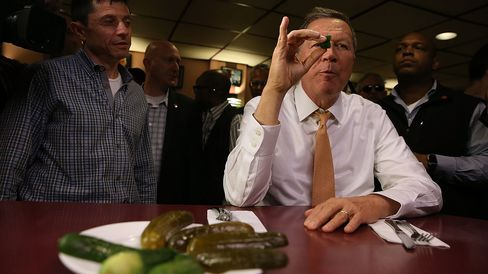 Republican presidential candidate John Kasich eats a pickle at PJ Bernstein Deli on April 16, 2016, in New York City.