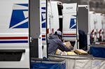 A letter carrier prepares a vehicle for deliveries at the United States Postal Service.