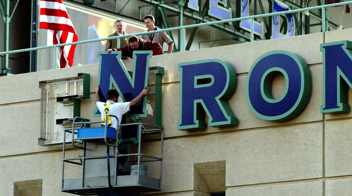 Workers taking down Enron building sign