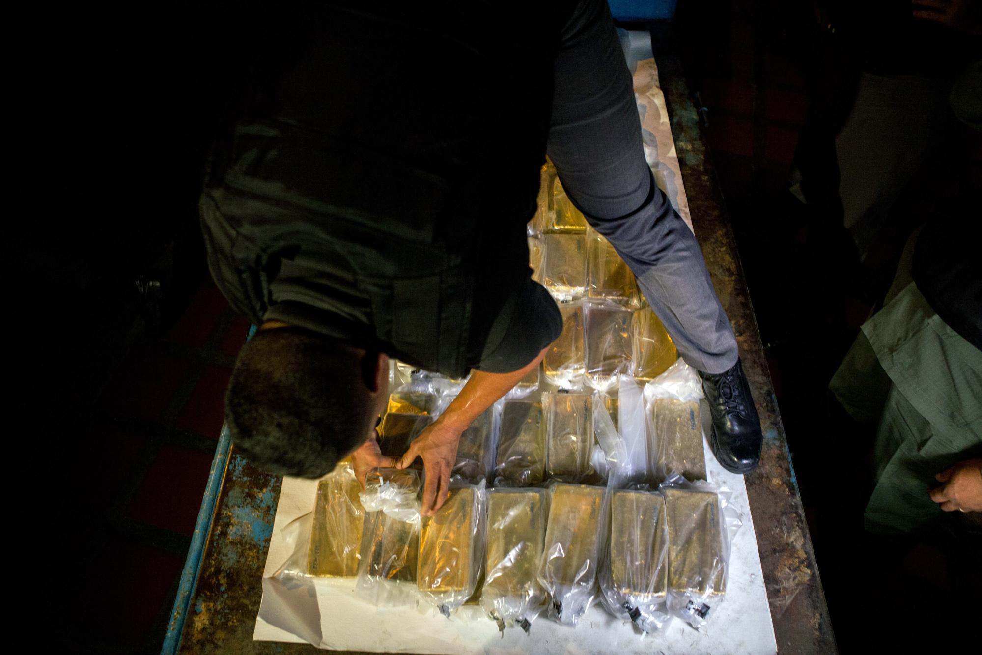 Un oficial descarga barras de oro de un avión para transportarlas hacia el Banco Central de Venezuela.