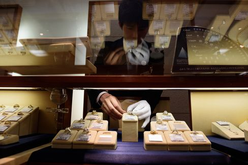 An employee arranges a used diamond ring inside the Komehyo Co. Shinjuku store in Tokyo. Photographer: Akio Kon/Bloomberg