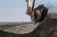An excavator scoops up coal in an open pit