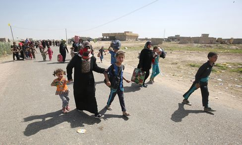 Iraqis walk towards a military point as they flee the violence in their village of Saqlawiyah, north west of Fallujah, on June 3, 2016.