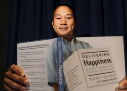 Zappos founder Tony Hsieh displays a copy of his autobiography Delivering Happiness.