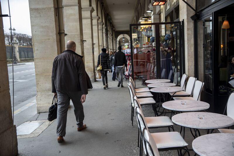 I pedoni passano tavoli vuoti in una terrazza del caffè a Parigi.